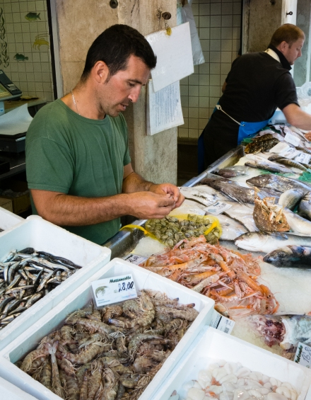Fish monger at the Rialto Market, Venice, Italy