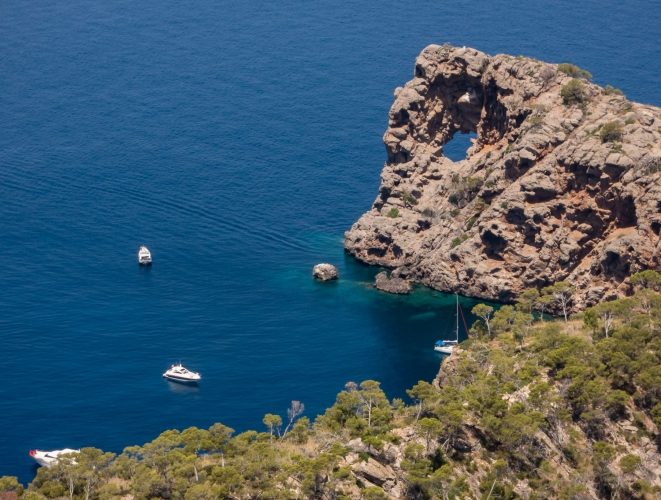 "A famous anchorage in the Balearic Sea, near Port de Sóllerr, Mallorca, with the ""doughnut hole"" rock formation"