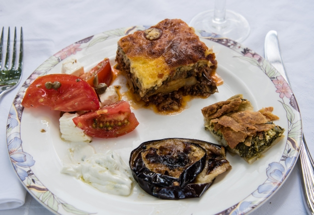 Enjoying the fruits of our cooking -- Greek mousaka, spanakopita, fried eggplant, Greek tzatziki, and fresh tomatoes with feta cheese