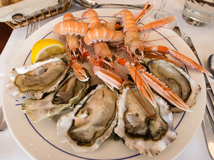 Langoustines and fresh oysters, lobster menu first course at L'Amiral Restaurant, Concarneau, France