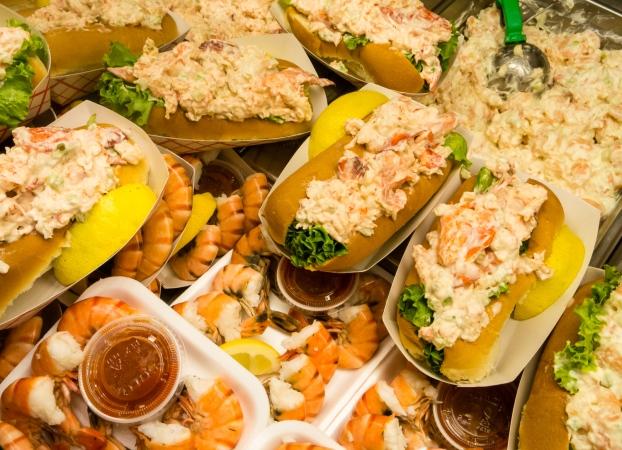 Hot buttered lobster rolls and fresh shrimp for sale in Faneuil Hall market, Boston, Massachusetts, USA