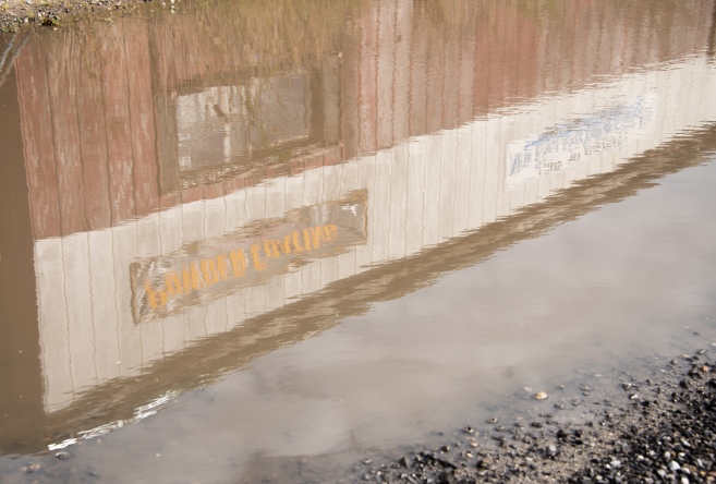 Rain puddle reflection of weathered building signs near the harbor, Portland, Maine, USA