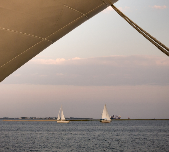Sailboats in the harbor at sunset, framed by our ship at the pier in Charleston, South Carolina, USA