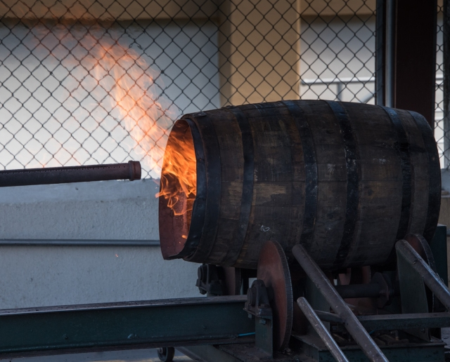 Charring an American oak aging barrel in the refurbishment process at the Ron Barceló factory, Santo Domingo, Dominican Republic