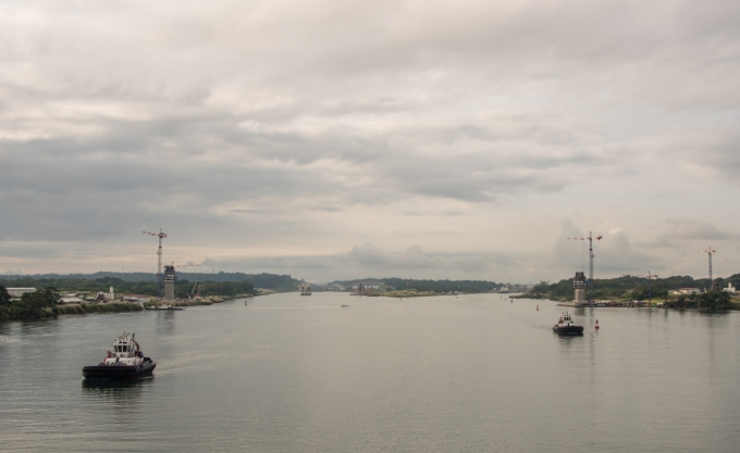 Having sailed past Colon, Panama, the entrance to the Panama Canal's first locks are now visible on the right hand side, past the red channel buoys (with the foundations of a new bridge to span the channels visible in the foreground), Panama