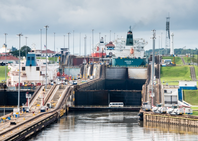 Sailing into position to enter the first of the three Gatun locks of the Panama Canal on the starboard (right-hand) side; the lock's water level is at sea level in this view, Panama