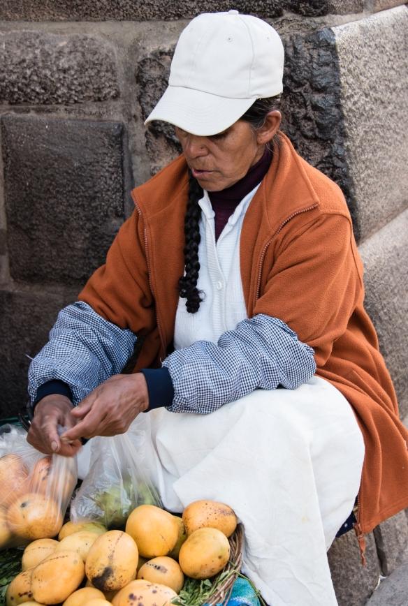 Local woman selling fruit on a street corner in Cuzco, Peru