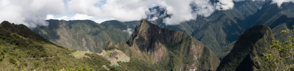 The incredibly stunning panoramic view from the Inca Trail Sun Gate looking down at Machu Picchu, Peru, built into the man-made plateau of the mountains