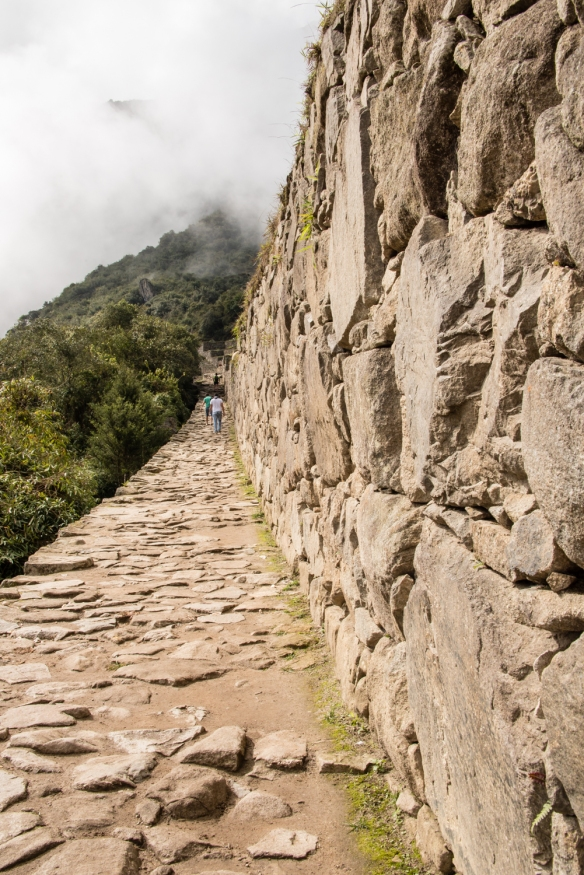 The last section of the Inca Trail, arriving at Machu Picchu, Peru, after descending from the Sun Gate (near the crest of the hill, barely visible in the clouds, upper left)