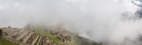 The typical, early morning panorama of Machu Picchu, Peru, the city hidden in the clouds of the Andes Mountains