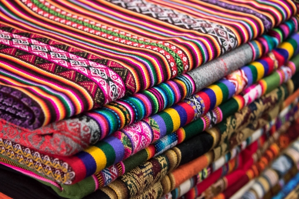 The bright colors signal synthetic dyes and machine weaving, Mercado San Pedro, Cuzco, Peru