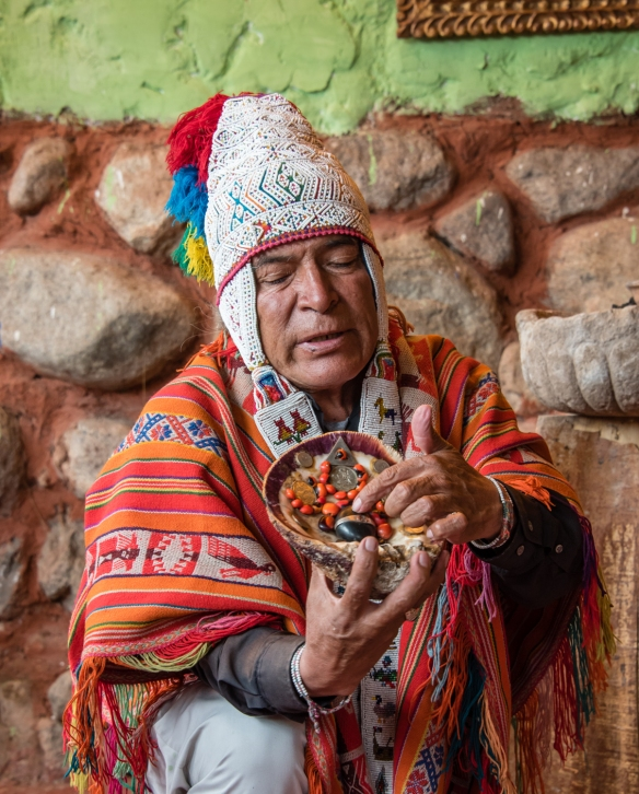 "The medicine man (Andean ""priest"") blesses an Andean amulet during the Despacho ceremony (Andean Ritual to Mother Earth), Ollantaytambo, Peru"