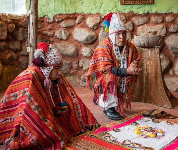 "The medicine man (Andean ""priest"") prepares to tie up the ritual offerings for burning during the Despacho ceremony (Andean Ritual to Mother Earth), Ollantaytambo, Peru"