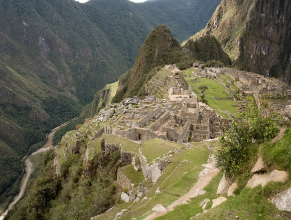 Wide-angle elevated view of Machu Picchu from the upper agricultural terraces showing the Urubamba River on the west (left side), the granite quarry and the two urban sectors adjacent to the main square, Peru