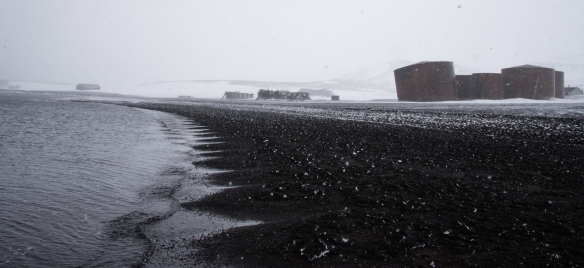 Abandoned whaling station buildings and whale oil tanks viewed in a blizzard, Deception Island, South Shetlands Archipelago, northwest of the northern tip of the Antarctic Peninsula