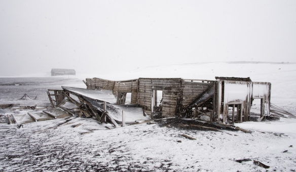 An abaandoned whaling station biuilding in ruins viewed in a blizzard, Deception Island, South Shetlands Archipelago, northwest of the northern tip of the Antarctic Peninsula