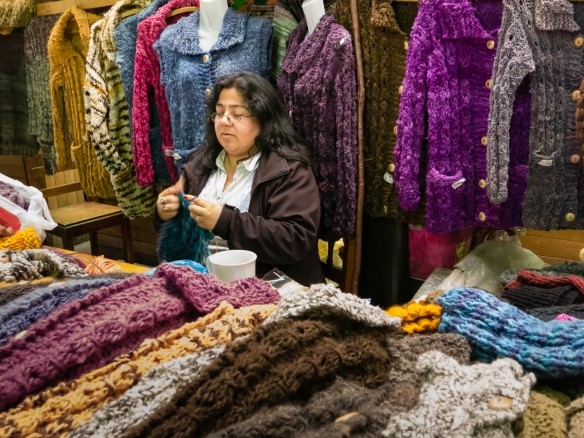 One of many knitters with warm woolen sweaters and scarves for sale in the local farmers' market, Castro, Chiloe Island, Chile