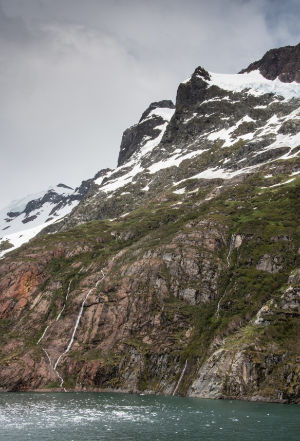 Waterfalls of melting mountain snow flowing into Keats Sound, Alberto de Agostini National Park, Patagonia, Chile