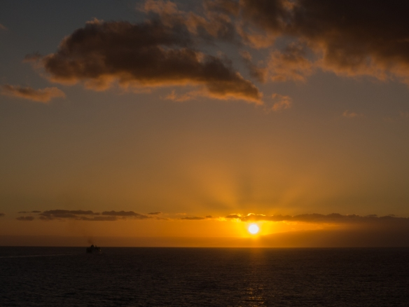 A colorful sunset from our ship (anchored) as another ship sailed west at dinnertime from Los Cristianos, Tenerife, Canary Islands