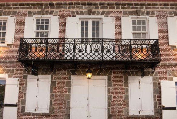 Classical French-style wrought-iron balcony on an old brick building in the historic downtown street in Gustavia, Saint Barthélemy (St. Barth's), Caribbean Sea