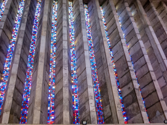Colored beams of light coming from the stained glass windows streaming into the interior of Notre Dame de Lourdes Catholic Church, Casablanca, Morocco
