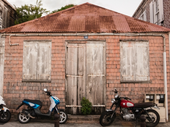 Contemprary motorbikes in front of an old building in the historic downtown street in Gustavia, Saint Barthélemy (St. Barth's), Caribbean Sea