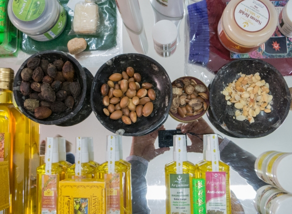 Moroccan argan nuts – whole, shelled, halved, and sliced-roasted in the center bowls – and argan oil, creams, etc. for sale in Casablanca, Morocco