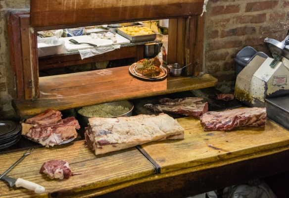 One entree from the kitchen ready for serving and many cuts of fine Argentinian beef awaiting the grill, El Obrero, in La Boca, Buenos Aires, Argentina
