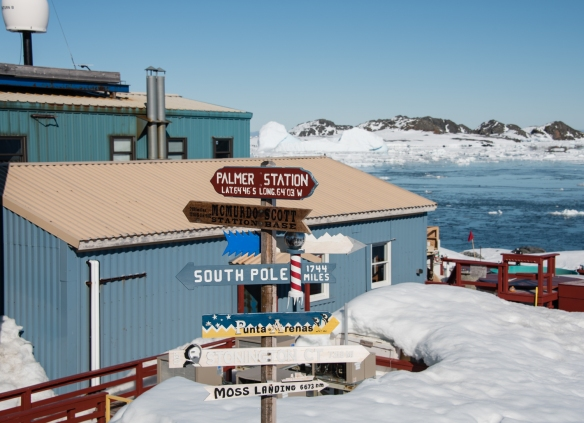 Some of the buildings of the U.S. Antarctic Program's Palmer Station, with the directional sign to other research stations, in Arthur Harbour on Avers Island, Antarctica