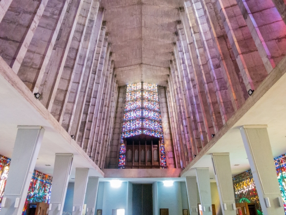 The open, airy interior is lit up by the colored beams of light that filter through stained glass windows which cover the two entire side walls, Notre Dame de Lourdes Catholic Church, Casablanca, Morocco