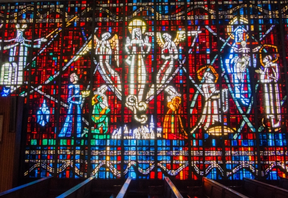 The stained glass windows are cut on a red and blue colored background, reminiscent of typical Moroccan carpets, and represent different images of the Virgin Mary, Notre Dame de Lourdes Catholic Church, Casablanca, Morocco