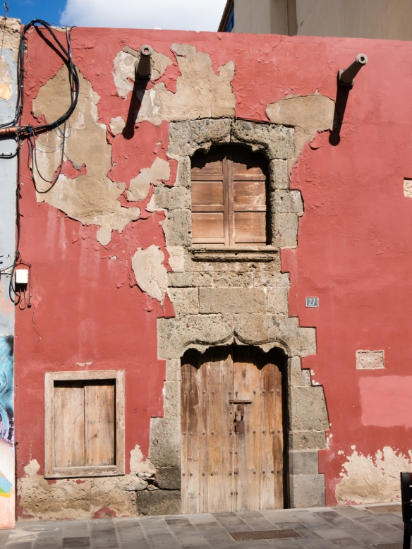 The weather-beaten facade of an old Spanish-style building, next to a modern building, in the historic Vegueta district, Las Palmas, Gran Canaria, Canary Islands