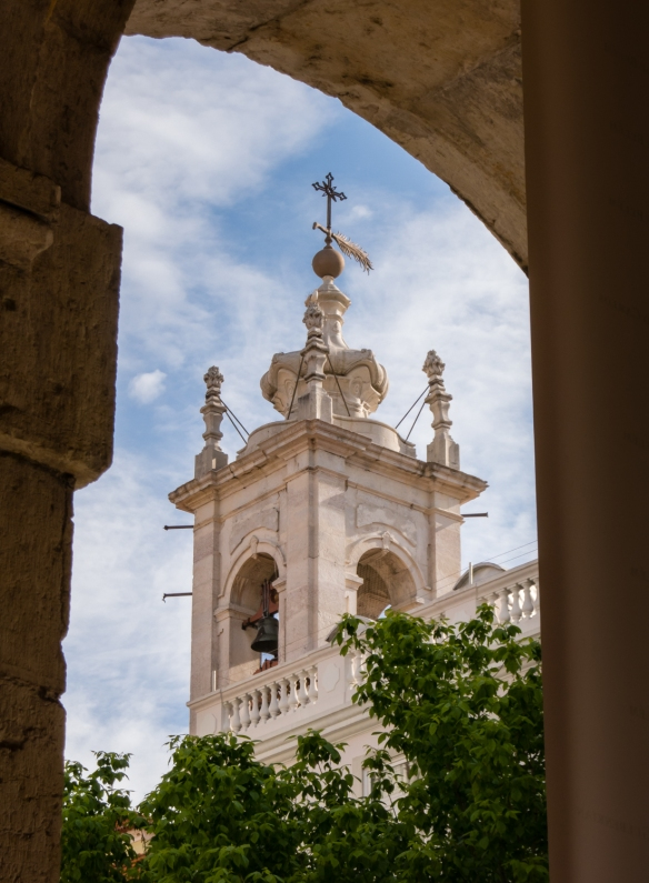 Bell tower of a church visible through the entrance arches of Teatro Nacional de São Carlos (National Theatre of Saint Charles), the opera house in the Chiado District, Lisbon, Portugal
