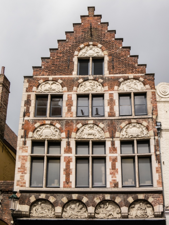A residence built in 1654 with half-oval sculptural inlays on the brick facade, Bruges, Belgium