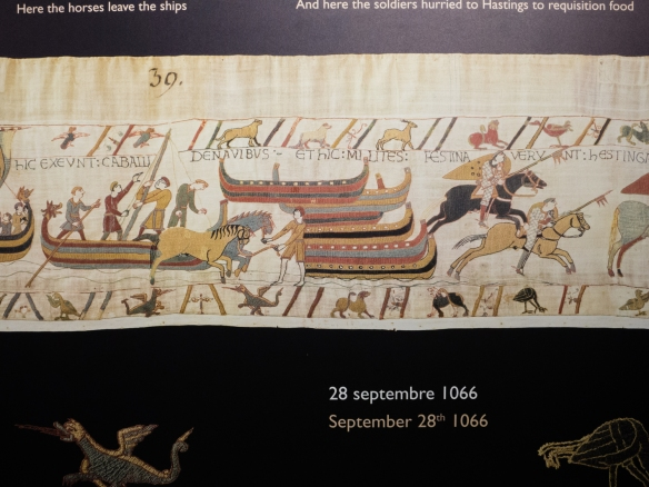 "A scene in a reproduction of the Bayeux Tapestry depicting events on 28 September 1066 -- ""Here the horses leave the ships"" and ""And here the soldiers hurried to Hastings to requisition food"", Bayeux, Normandy region, France"