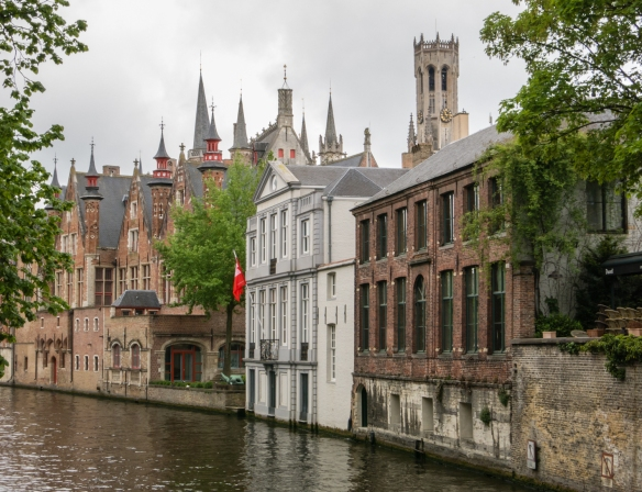 A typical canal scene with the Bruges Belfry visible in the skyline, Bruges, Belgium