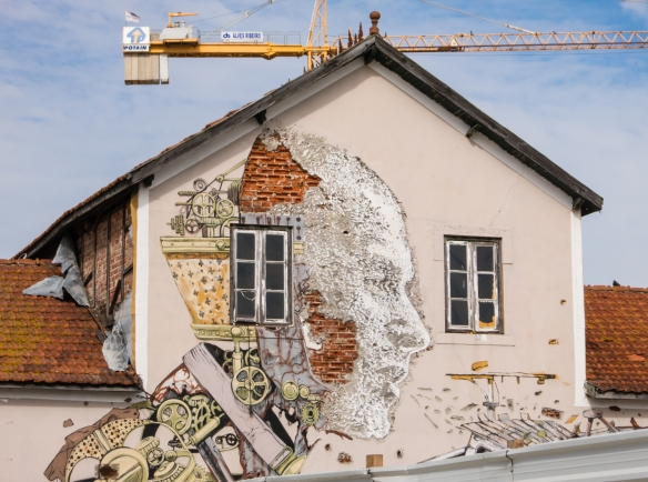"An artist used the facade of an historic building near the Port of Lisbon and the Tagus River as his ""canvas"", in the Alfama district of Lisbon, Portugal"