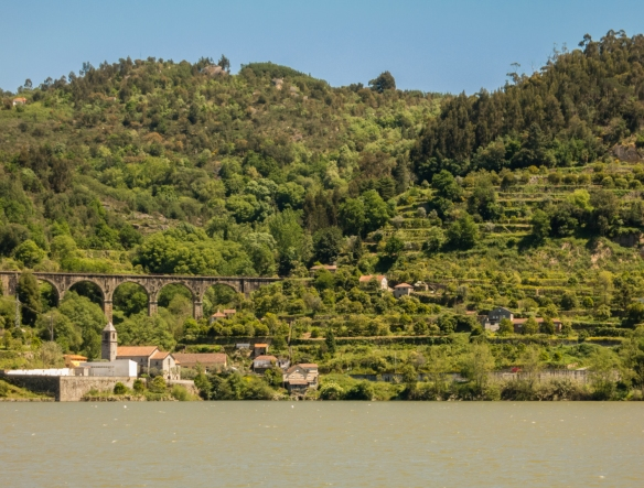 An old aqueduct and vineyards seen from our yacht sailing up the Douro River, heading upstream to the Douro Valley, Portugal