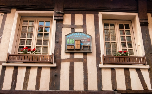 "Closeup detail of a business ""nameplate"" on the façade of a half-timbered style building in the old town of Honfleur, Normandy region, France"