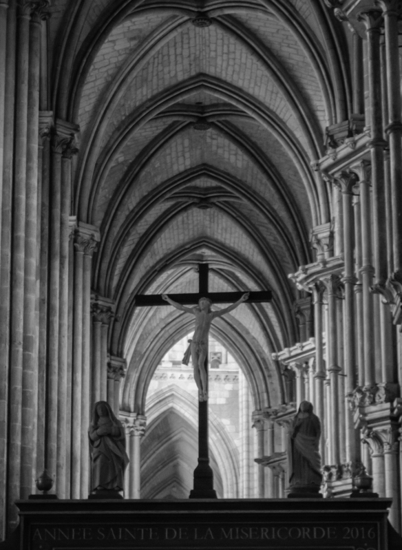 One of many crosses in Rouen Cathedral, seen as we stood in the rear of the cathedral during morning mass (black and white photograph), Rouen, Normandy region, France
