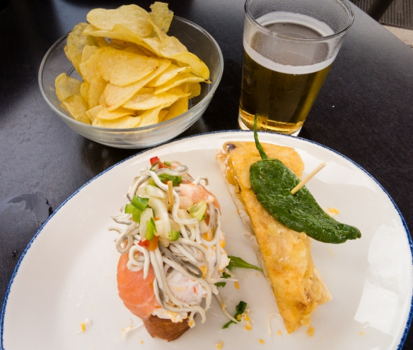 Smoked salmon and seafood along with a Spanish tortilla (potatoes) topped with a pepper tapas (locally called pinchos) at Casa Lita in Santander, Spain