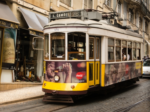 "The typical little yellow, historic electric-trolley, ""eléctrico 28"" is legendary now and tram 28 is a tourist attraction in itself, Lisbon, Portugal"