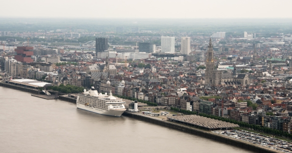 The view from our helicopter, looking northeast, over our ship, docked on the Schelde River, to the waterfront and historic center of Antwerp with the magnificent, soaring Cathedral of Our Lady's spire on the right; Antwerp, Belgium