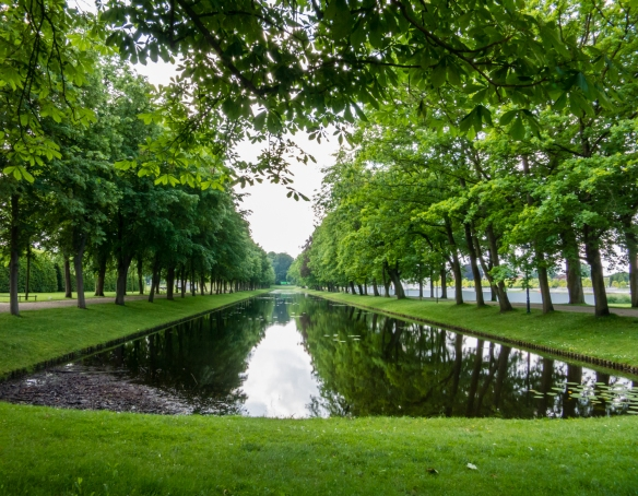 A peaceful, tree-lined pond in the gardens on the southern end of Scholss Schwerin (Schwerin Castle), Schwerin, Germany