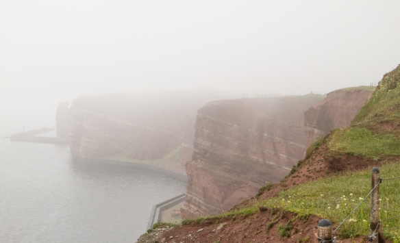 """Helgoland, Germany's main island (of the two) is well known for its iron-rich, reddish, tall cliffs, photographed here in the rain on the Westklippe (western cliff) from the trail along the """"Oberland"""" (upper land) section of the city"""