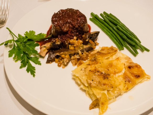 The entrée, prepared by our co-hosts, of filet mignon with wild mushrooms and a Cabernet Sauvignon sauce with Dauphinoise potatoes & haricot verts for a dinner party in our apartment on the ship for friends while transiting the Kiel Canal, Germany