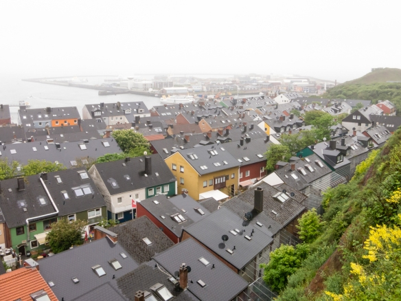 View of homes, shops and restaurants along the eastern waterfront in the Unterland (lowerland) section of town, photographed from the Oberland (upper land) section of the city, Helgoland, Germany