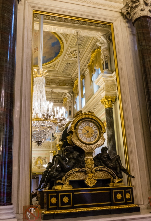 An elaborate 17th century mantle clock in front of a mirror showing the decorations typical of many of the exhibition rooms in the European Masterpieces permanent exhibition wing of the Hermitage Museum, St. Petersburg, Russia