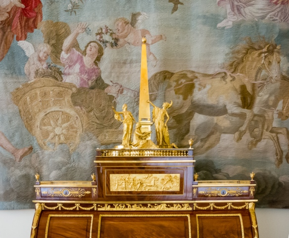 An elaborately gilded desk with a gold statue in front of a hanging tapestry, The Winter Palace, St. Petersburg, Russia