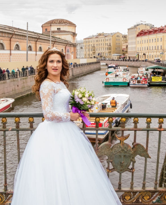 It is traditional for brides to visit many of the iconic sites in the city for portraits in their wedding gowns – here along a canal, with St. Isaac's Cathedral (on her right) out of sight from the angle of this portrait, St. Petersburg, Russia